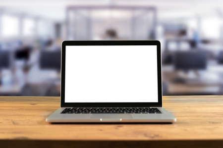 Maquette d'ordinateur portable à écran blanc sur une table en bois dans un espace de travail collaboratif. Banque d'images