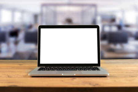 Mockup-Laptop mit leerem Bildschirm auf Holztisch im Co-Working-Raum. Standard-Bild