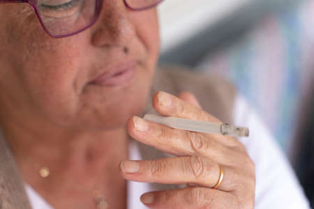 closeup of older woman holding a cigarette in her hands