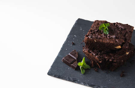 Stacked pieces of walnut brownies on a slate platter and white background, decorated with walnuts, chocolate and mint leaves, with copy space