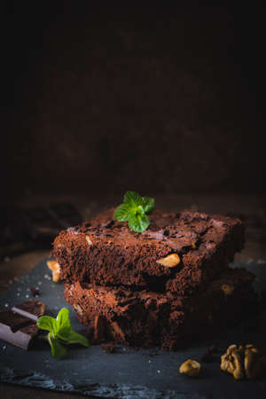 Stacked pieces of walnut brownies on a slate platter and dark brown background, decorated with walnuts, chocolate and mint leaves, vertical with copy space Stock Photo