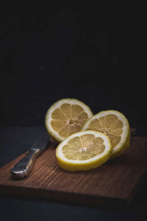 Lemon cut into three pieces, lying with a knife on a wooden slat, vertical with copy space and black background