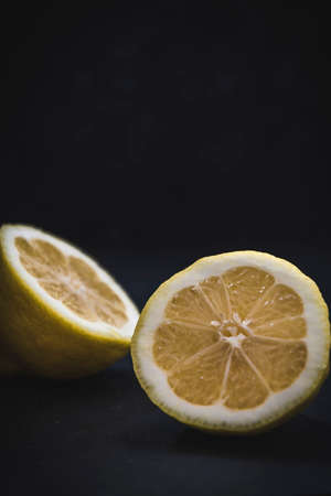 Lemon cut into two halfs, lying on dark background, vertical with copy space 스톡 콘텐츠