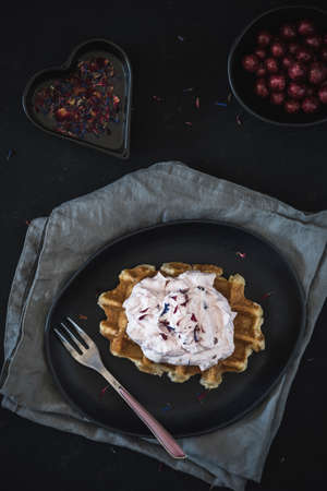 Belgian waffle with rose cranberry cream, lying on a black plate and gray napkins, decorated with rose fork and colored eatible petals