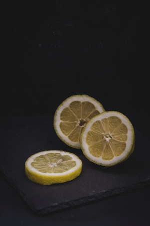 Lemon cut into three pieces, lying on a black slate platter, vertical with copy space