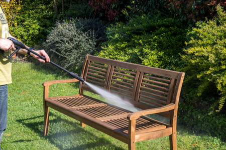 Man cleaning wooden garden bench with a high pressure cleaner in spring time.