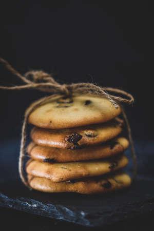 Piled homemade chocolate cookies on a slate plate on dark background. Closeup.