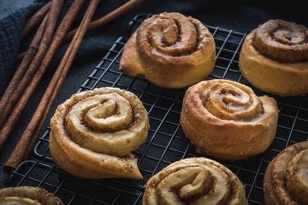 Homemade cinnamon rolls on a colling rack with cinnamon sticks on dark blue background.