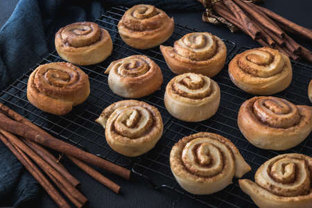 Homemade cinnamon rolls on a colling rack with cinnamon sticks and dark blue cloth.