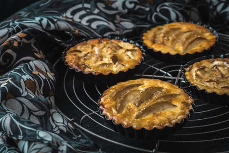 Baked apple tartlets in black tart dishes on a cooling rack with black and white patterned cloth as background. Archivio Fotografico