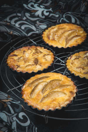 Baked apple tartlets in black tart dishes on a cooling rack with patterned cloth. Vertical closeup. Archivio Fotografico
