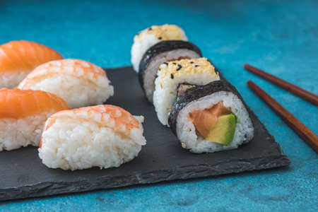 Variety of nigiri and maki shushi on slate and wooden chopsticks on blue background