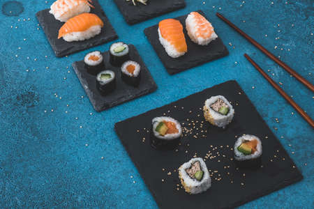 Variation of nigiri and maki shushi on slate plates, ginger and wooden chopsticks on blue background