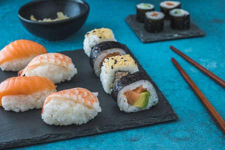 Variety of nigiri and maki shushi on slate, ginger and wooden chopsticks on blue background