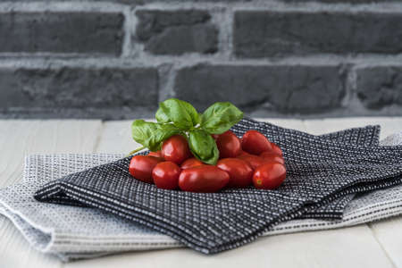 Ripe cherry tomatoes with basil branch on black and white tea towels against a gray stone background