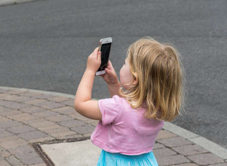 Little girl takes a photo with a smartphone 免版税图像