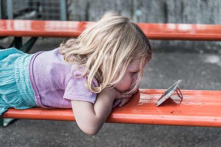 Little blond girl lies on a bench watching a video on a smartphone