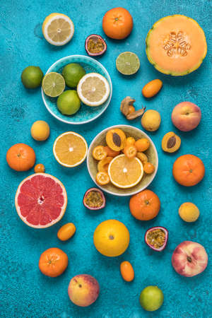 Variety of tropical colorful summer fruits on blue background, vertical top view