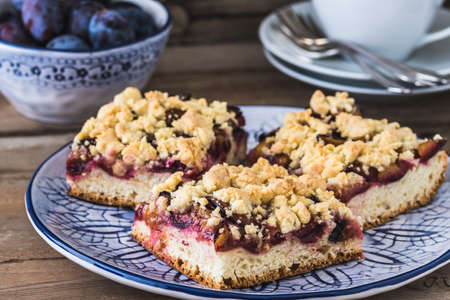Three pieces of plum cake with crumble on a bluewhite plate on a wooden table 免版税图像