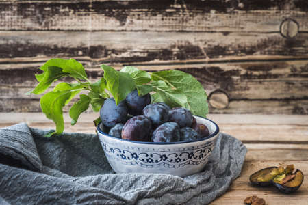 Little bowl with ripe plums on wooden background 免版税图像