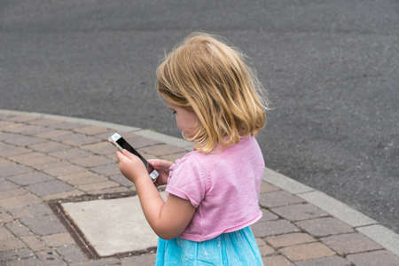 Little girl looking at the smartphone in her hand