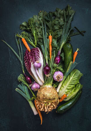Variety of vegetables on dark background, vertical top view, concept of healthy eating