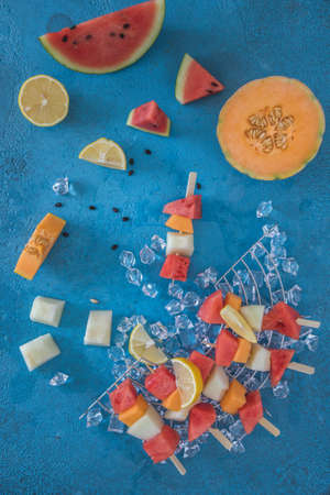 Melon skewers on ice on blue background, vertical top view