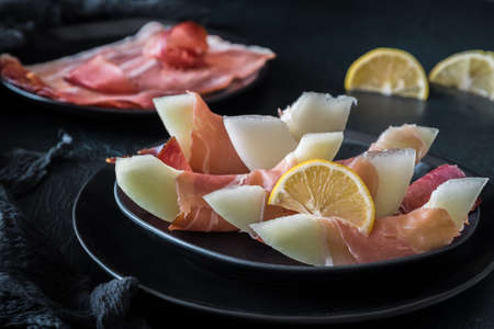 Honeydew melon wrapped in ham served on a black plate