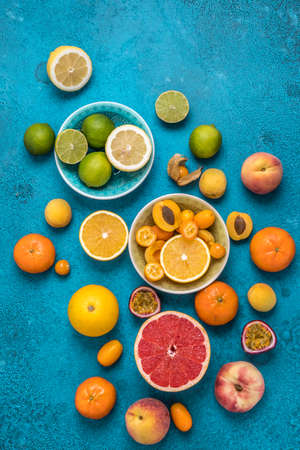 Tropical colorful summer fruits on blue background, vertical top view with copy space