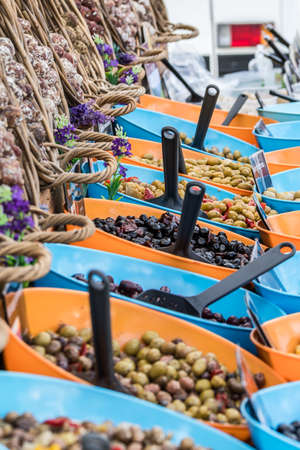 Variety of olives in blue and orange bowls and baskets with salami on a market stand