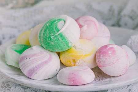 White plate with colorful little meringues