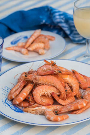 Plate with prawns on a blue and white table and background, vertical stock photo