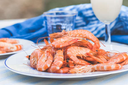 Plate with prawns and a glass with aperitif on a blue and white table 免版税图像