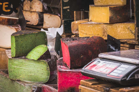 Variety of colorful cheese at a market stand, naturally colored by tomatoes and pesto