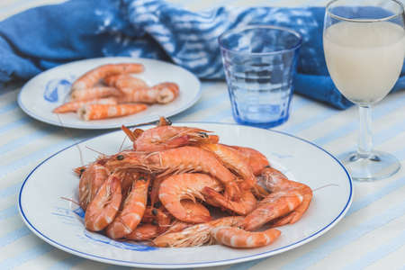 Plate with prawns on a blue and white table and background, smaller plate with peeled prawns in the background