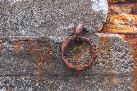 Rusty ring for the mooring of a fishing boat on an old dock 免版税图像