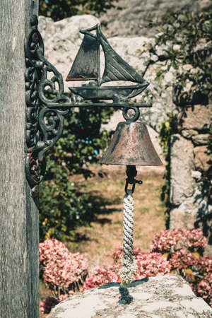 Rusty vintage metal bell with metal ship on the bracket, hanging on a wooden beam over a garden door