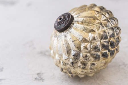 Old golden textured christmas bauble on white patterned background with copy space