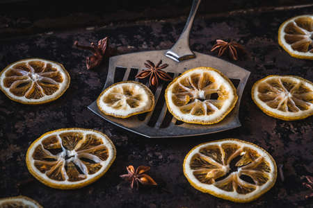 Three lemons and oranges slices on an old baking sheet. Used for christmas decoration.