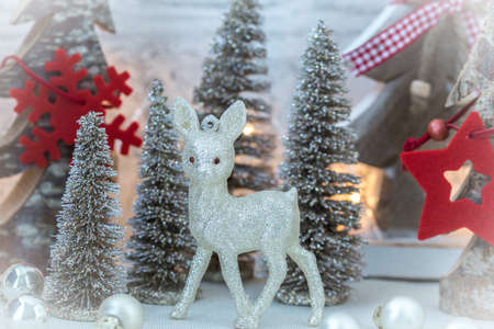 Glittering little deer in front of various fir trees as a Christmas decoration