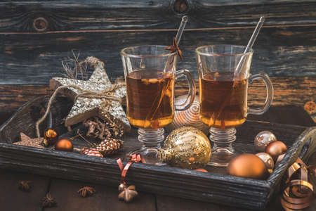 Two glasses with tea on a Christmas decorated wooden tray