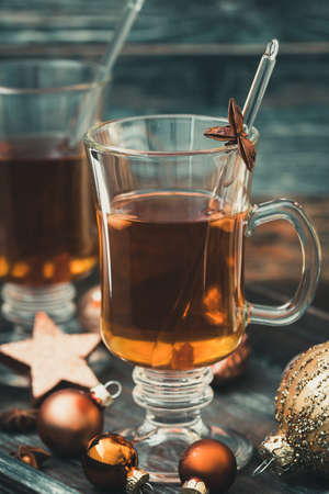 Glass with tea on a Christmas decorated wooden tray. Vertical stock photo.