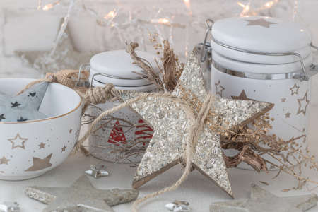 White porcelain jars and bowl with gold and silver christmas decoration and warm light