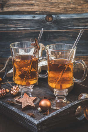 Two glasses with tea on a Christmas decorated wooden tray. Vertical stock photo.