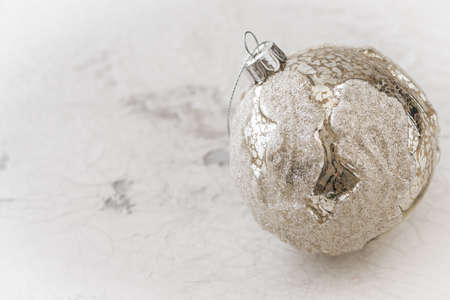Silver textured christmas bauble on white patterned background with copy space