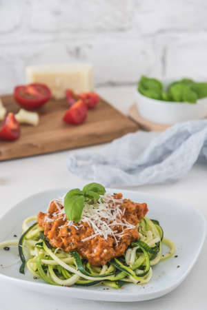 Zoodles bolognese: zucchini noodles with meat or vegan soy meat sauce and parmesan. For low carb, keto, paleo nutrition. Vertical stock photo with copy space.