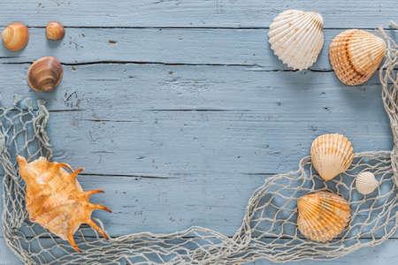 Sseashells and fishing net on blue wooden background 免版税图像
