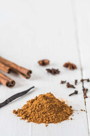 Baking spices like cinnamon, star anise, and vanilla bean on white wooden table. Vertical stock photo with copy space.
