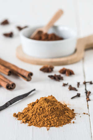Baking spices like cinnamon, star anise, cocoa and vanilla bean on white wooden table. Vertical stock photo.