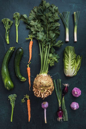 Variety of vegetables on dark background, vertical top view, concept of vegetarian healthy eating